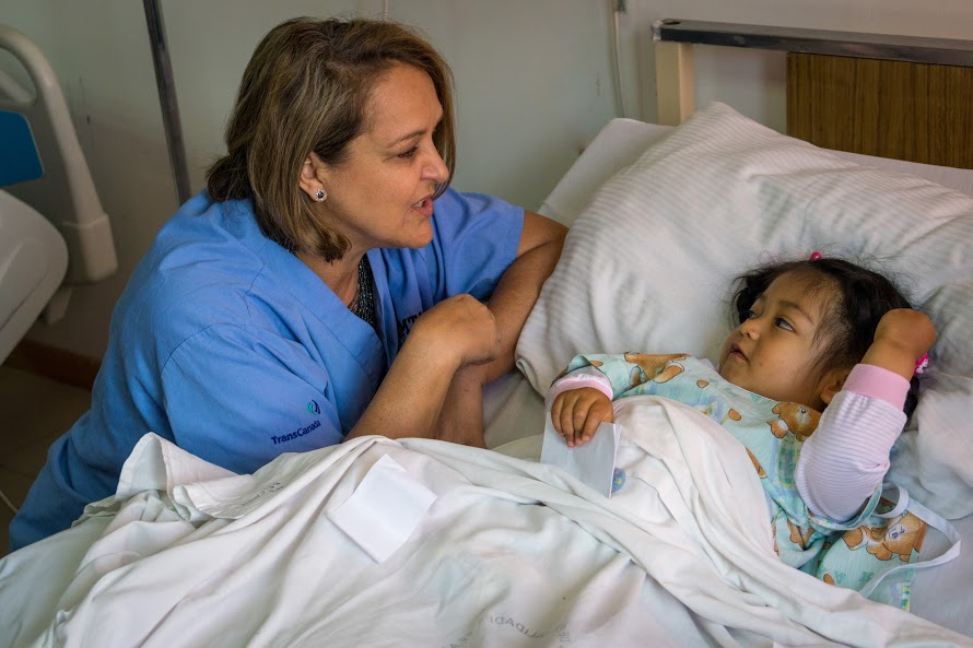 A CAMTA nurse talking to a child patient in bed